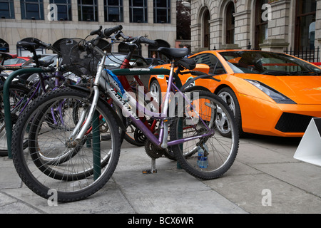 lamborghini sports car parked on pavement beside row of bicycles dublin republic of ireland illustrating wealth gap and social inequality