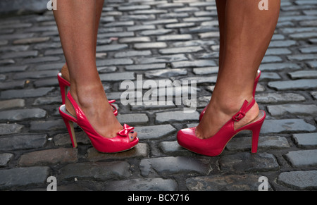 two young women wearing red high heeled shoes and fake tan on cobblestones on a night out in dublin republic of - Stock Photo