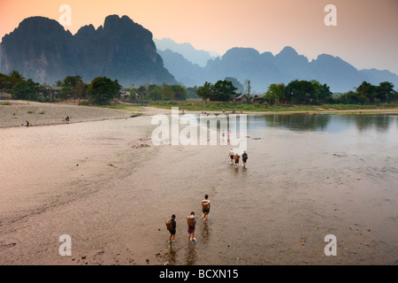 women wading the Nam Song River at Vang Vieng, Laos - Stock Photo