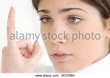 young woman, adhesive bandage on finger - Stock Photo
