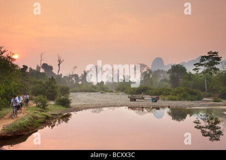 cyclists and a tractor at dawn; rush hour in the countryside near Vang Vieng, Laos - Stock Photo