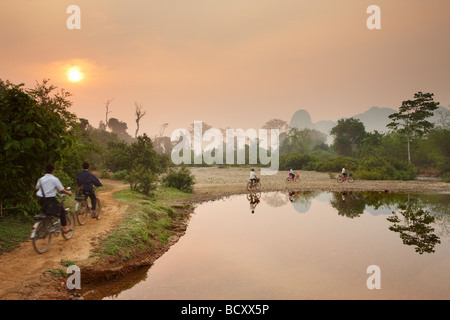 children cycling to school at dawn; rush hour in the countryside near Vang Vieng, Laos - Stock Photo