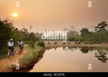 cyclists at dawn, rush hour in the countryside near Vang Vieng, Laos - Stock Photo