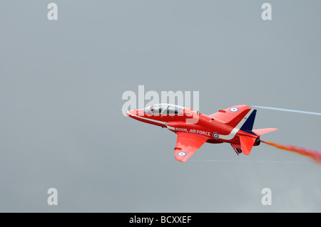 Red Arrows Hawk Trainer XX233, one of the Syncho pair, rehearses their display routine against a cloudy backdrop - Stock Photo