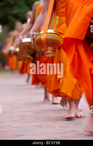 the procession of monks at dawn through the town to collect gifts of food, Luang Prabang, Laos - Stock Photo