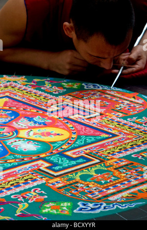 Tibetan monk making a temporary sand mandala - Stock Photo