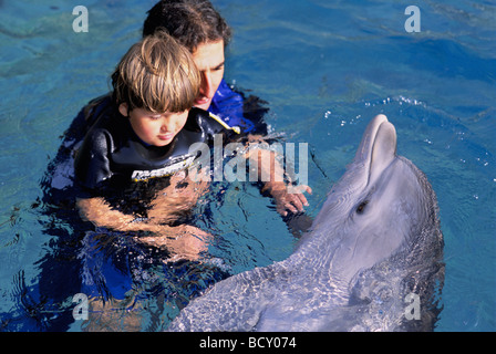 Autistic child receives therapy with dolphin trainer and Bottlenose Dolphin - Stock Photo