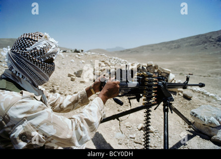 A Pakistani Anti Narcotics Force commando sets up a heavy machine gun for an ambush against heavily armed Afghan - Stock Photo