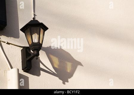 A traditional style wall mounted outdoor light with long lasting, low energy bulb, casting a shadow on the wall. - Stock Photo