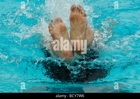 Swimmer pushing off during flip turn, view of bottoms of feet. - Stock Photo