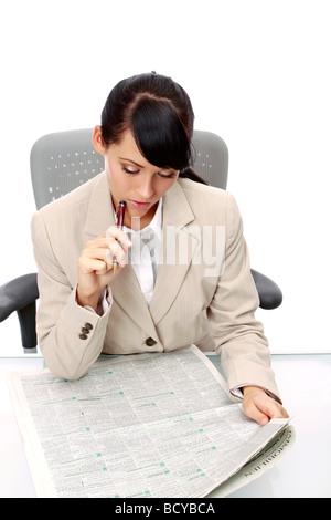 Junge Frau liest Anzeigen in der Zeitung Businesswoman reading newspaper - Stock Photo