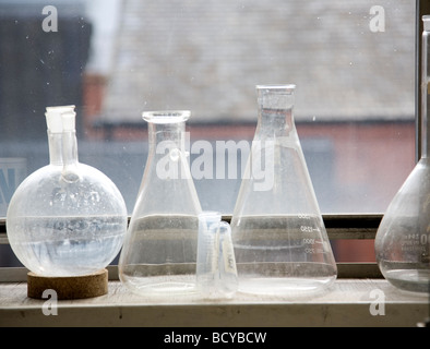 Glass beakers on window shelf - Stock Photo