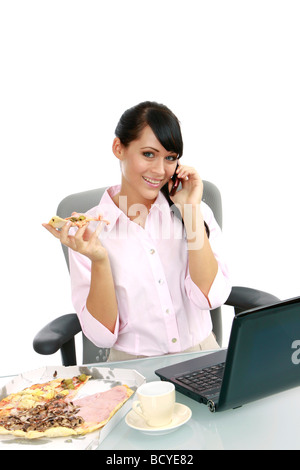 Junge Frau isst Pizza im Buero Businesswoman eating pizza in the office - Stock Photo