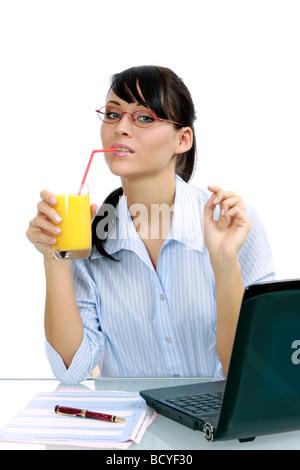 junge Geschaeftsfrau trinkt Saft im Buero young businesswoman enjoys orange juice in the office - Stock Photo