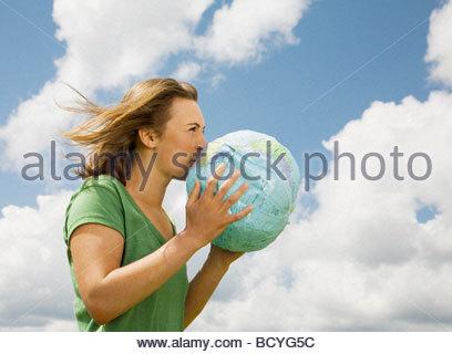 Woman Inflating Globe - Stock Photo