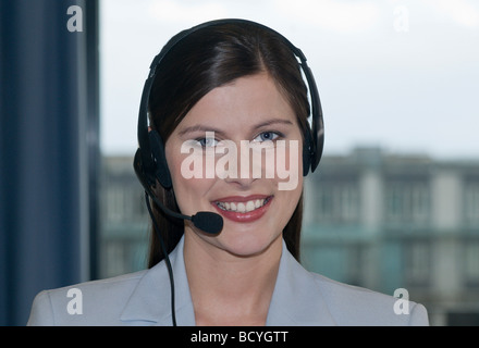 Businesswoman wearing headset, smiling - Stock Photo
