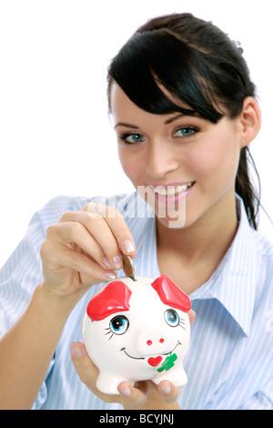junge Frau steckt Geld in ihr Sparschwein attractive woman banking euro coin in here piggybank - Stock Photo
