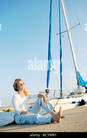 Woman relaxing on harbor next to boat - Stock Photo