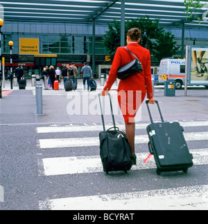Rear back view of an air hostess  woman with luggage on a crosswalk walking to Terminal 3 entrance at Heathrow airport - Stock Photo