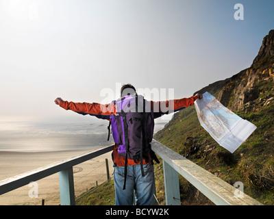 man hiking on cliff edge - Stock Photo