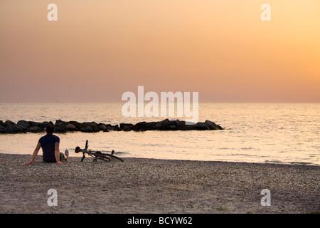 man sitting on beach facing the sea - Stock Photo