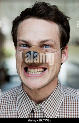 man with toy dog nose snarling - Stock Photo