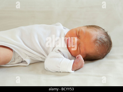 Baby lying on back sleeping - Stock Photo