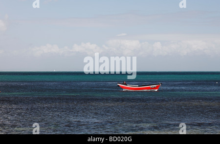 A loan fishing boat off Bembridge beach, Isle of Wight - Stock Photo