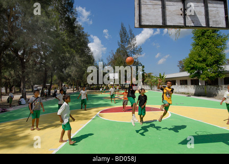 Schoolchildren playing on a basketball court built with foreign aid in the village of Viqueque Timor Leste - Stock Photo