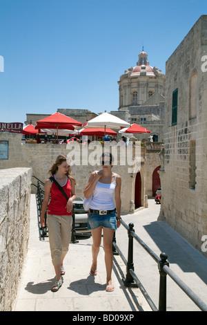 Two tourists walking along the old city wall, Mdina, Malta - Stock Photo