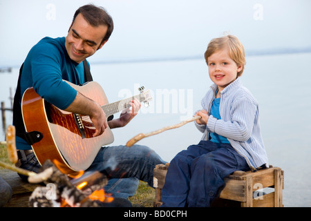 boy, man with guitar roasting sausages - Stock Photo