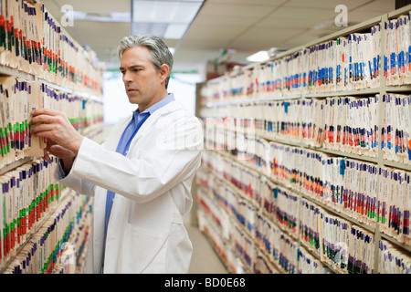 Male Doctor searching medical files - Stock Photo