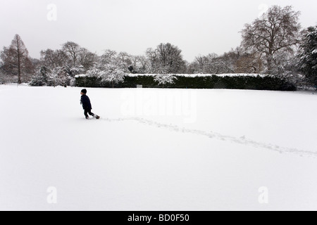 Boy walking through snow field - Stock Photo