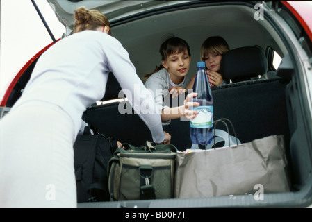 Woman organizing luggage in back of car, children looking over back seat - Stock Photo