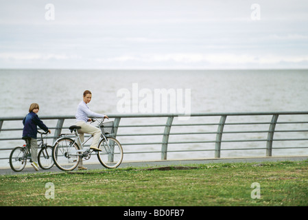 Mother and son riding bicycles at seaside park - Stock Photo
