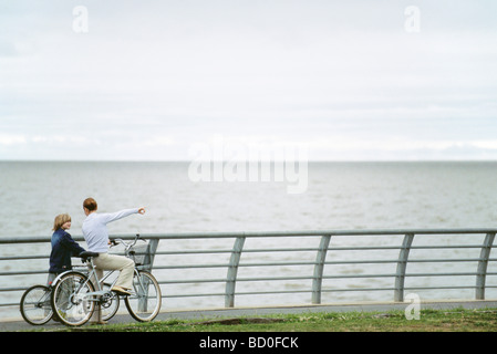 Mother and son on bicycle outing at seaside park, mother pointing to distance - Stock Photo