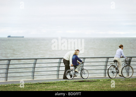 Father helping son learn to ride bicycle at seaside park, mother riding ahead - Stock Photo