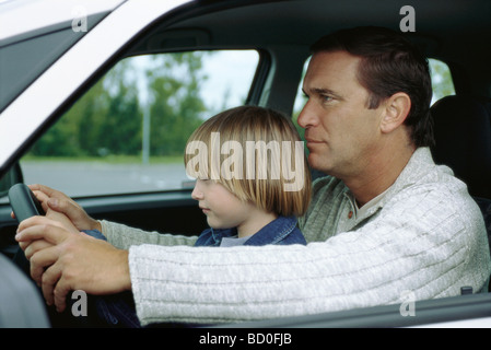 Man driving car with young son sitting on lap, both holding steering wheel - Stock Photo