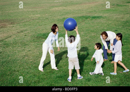 Family playing with ball in grassy field - Stock Photo