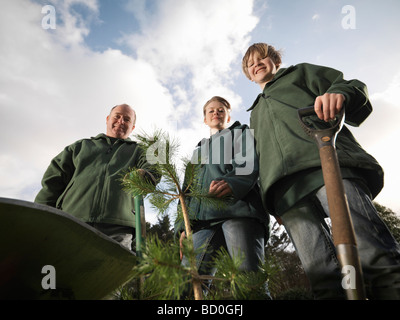 Man And Children With Young Trees - Stock Photo