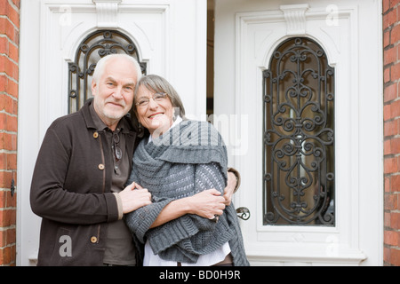 old couple standing at front door - Stock Photo