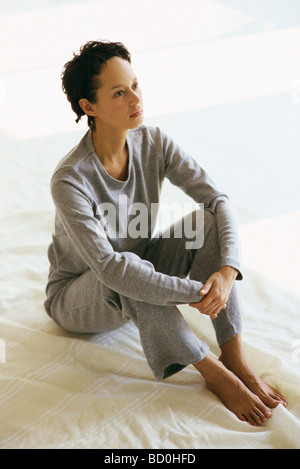 Women in athletic wear sitting on floor hugging knees looking away - Stock Photo