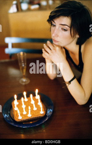 Woman at table with birthday cake looking away wistfully - Stock Photo