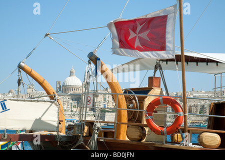 The maltese cross flag aboard a sailing boat with Valletta in the background, Malta - Stock Photo