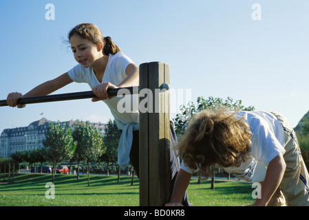 Girls playing on bars at park - Stock Photo