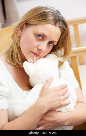 Sad Mother Sitting In Empty Nursery - Stock Photo