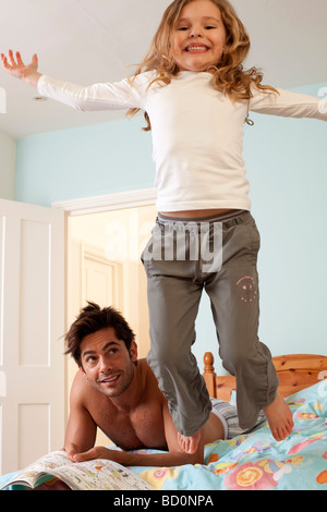 girl jumping off bed by father - Stock Photo