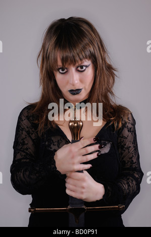 Studio portrait of a dark girl with longsword - Stock Photo