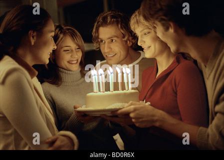 Friends gathered together around woman holding birthday cake - Stock Photo