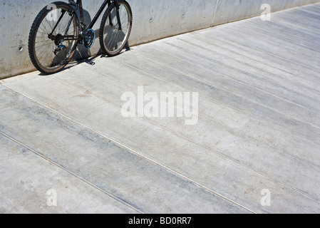 Bicycle with chain hanging loose leaning against wall, cropped view - Stock Photo